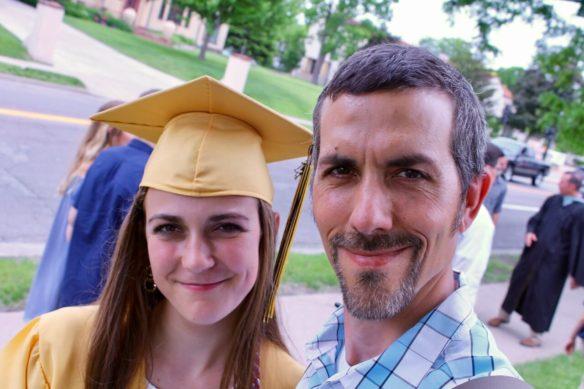 Helen in graduation regalia and Ed take a selfie