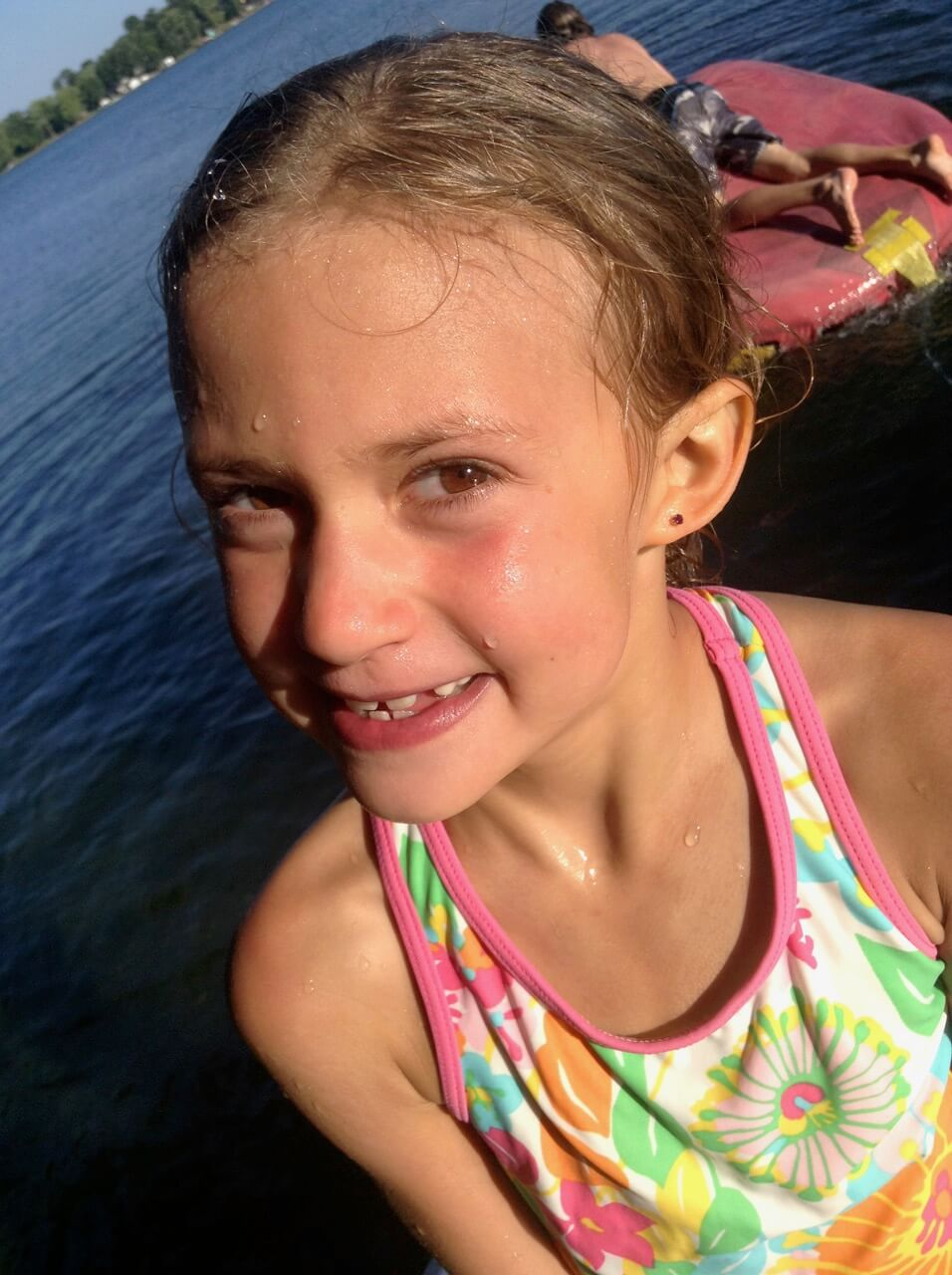 Lydia, wet, wearing a swim suit at the lake
